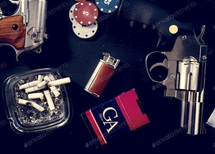 Guns, cigarettes, gambling coins on a table
