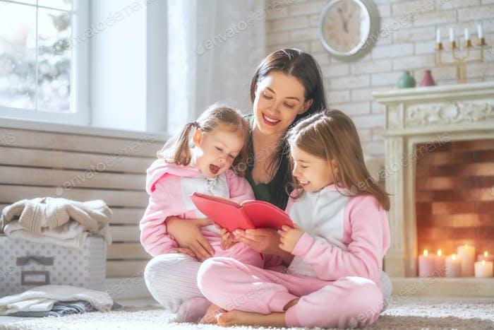 Mutter liest ein Buch, um ihre Töchter