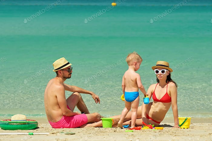 Family on beach. Toddler playing with mother and father.