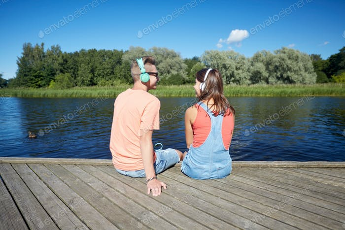 teenage couple with headphones on river berth