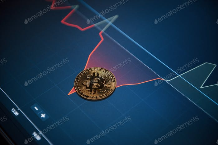 Picture of golden bitcoin lying on the display with graphs in office