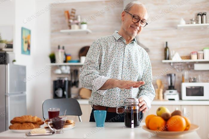 Senior man making coffee using french press during breakfast