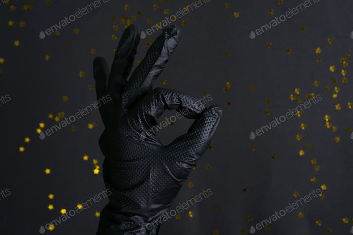 Woman's hand in a black latex glove for cleaning