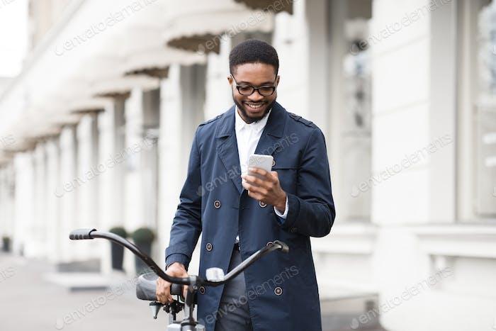 Weg zur Arbeit. Mann SMS am Telefon, stehend mit Fahrrad