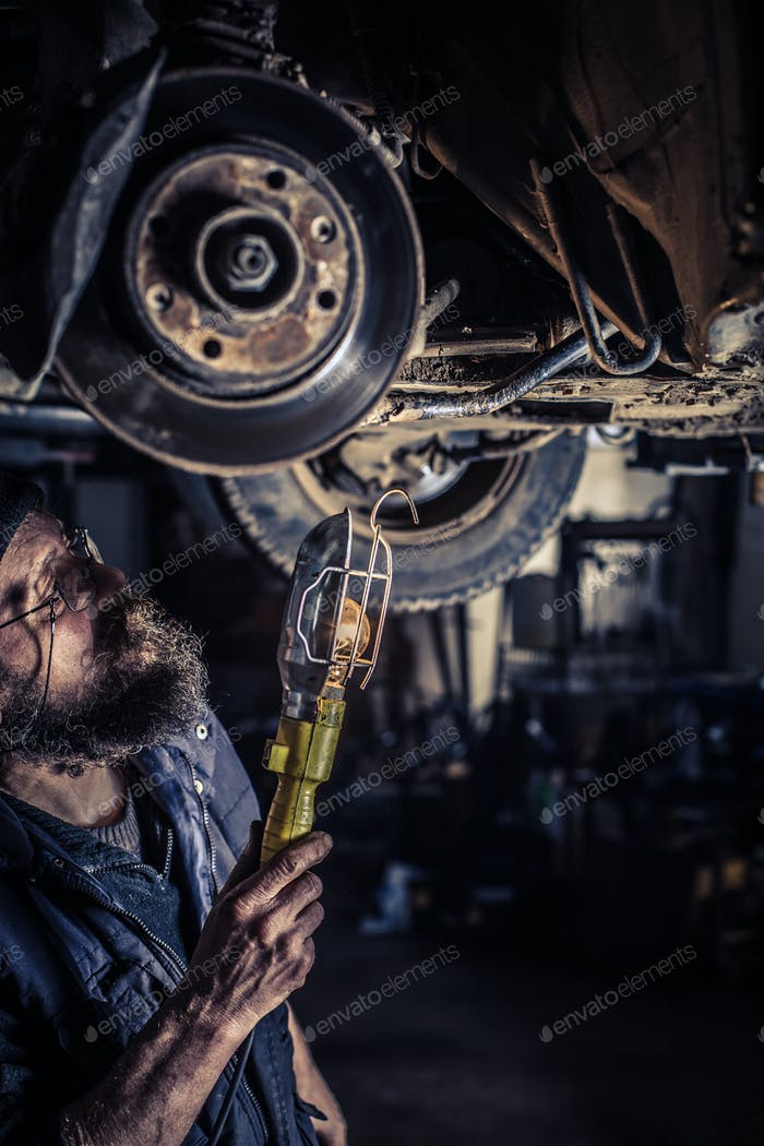 Mature mechanic at repair service station inspecting car suspen