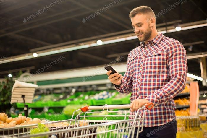 Handsome Man Holding Smartphone in Supermarket