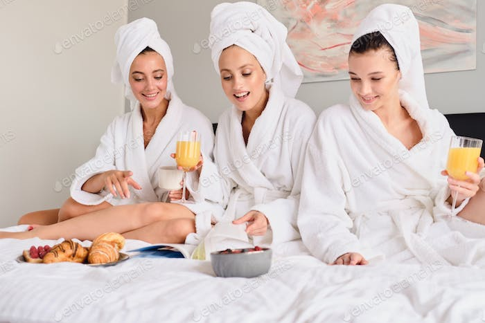 Young pretty smiling women in white bathrobes and towels on head happily reading book together