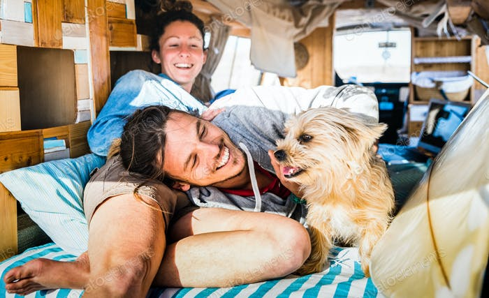 Hippie couple with funny dog traveling together on vintage minivan transport