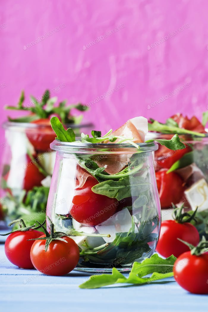 Salad with arugula, cheese, cherry tomatoes and prosciutto