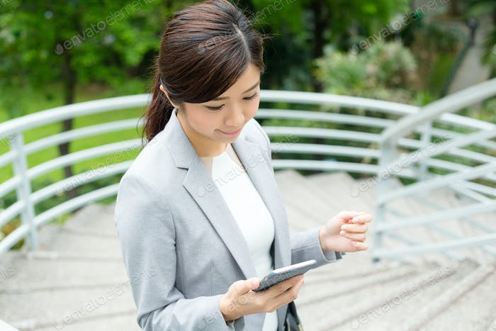 Asian Businesswoman read the message on cellphone and going up stair