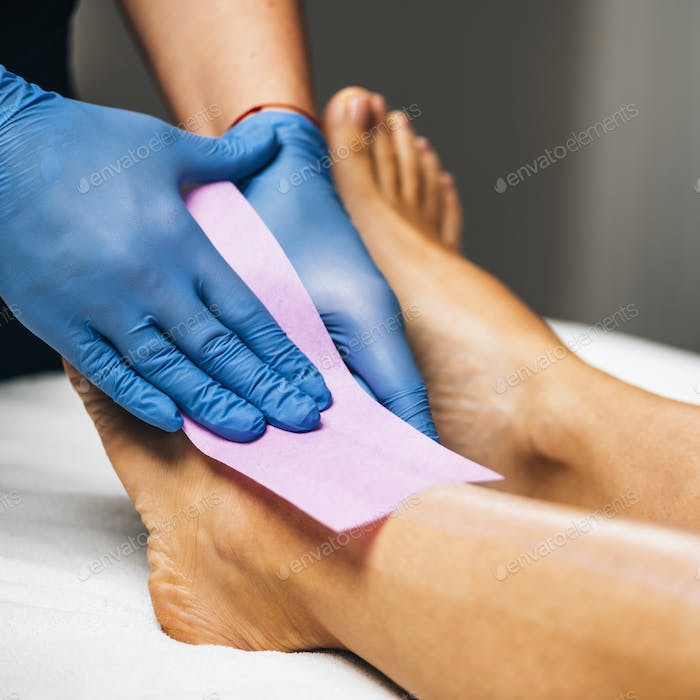 Waxing - Beautician Removing Unwanted Hair from Female Leg with Wax Strips