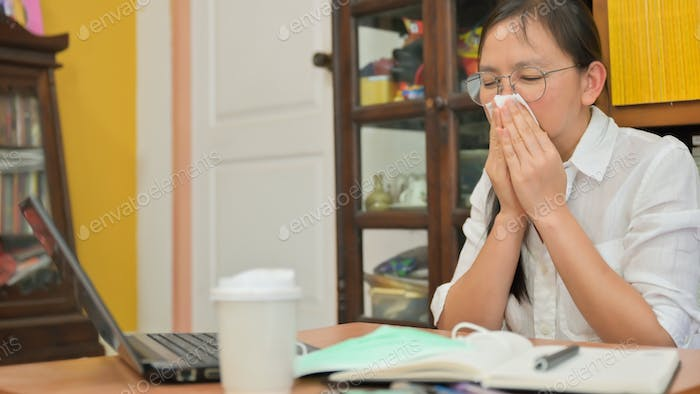 Asian woman uses a tissue to cover her face and sneeze.