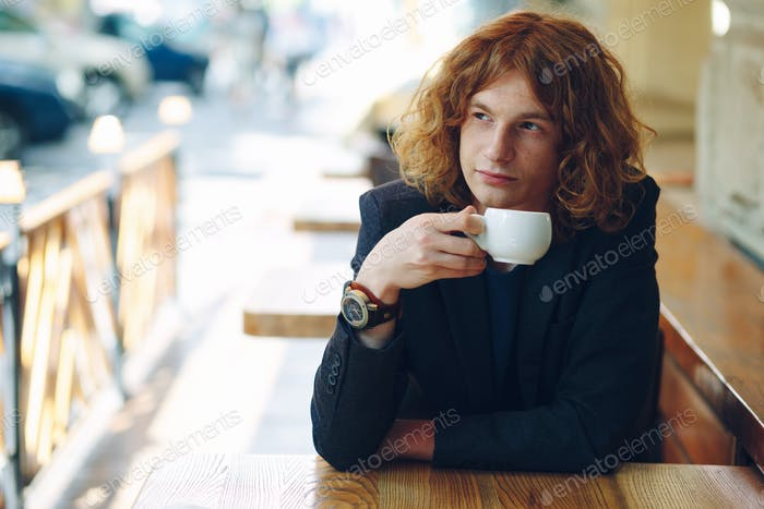 Portrait fashionable reddish man drinking coffee