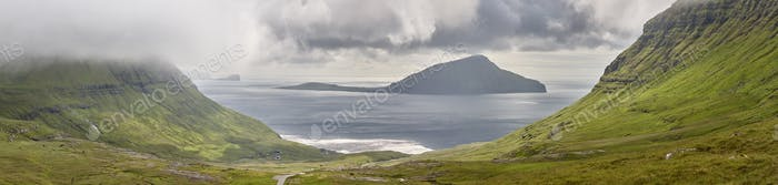 Panoramic picturesque green turf hills. Atlantic ocean in Faroe islands.