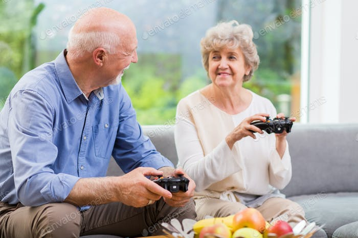 Grandmother and grandfather holding pads and playing video game
