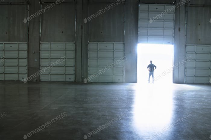 Commercial warehouse loading dock with employee standing in a doorway.