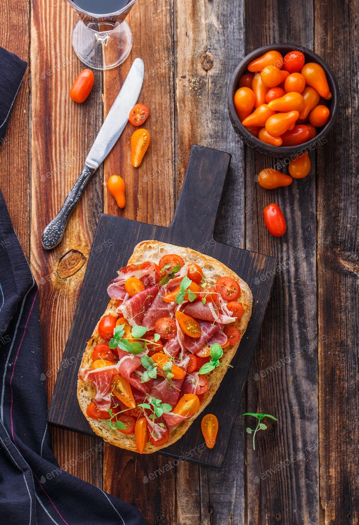 Grilled bread with jamon and cherry tomatoes, top view.
