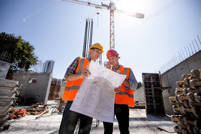 Structural engineer and construction manager in orange work vests and hard helmets discuss