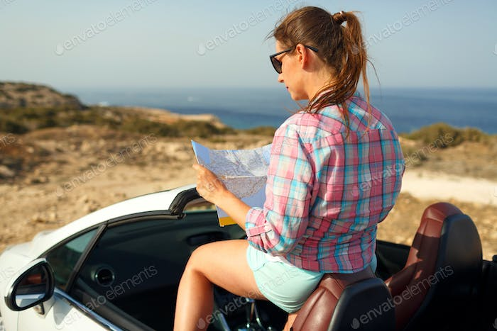 Young pretty woman see the map in the cabriolet