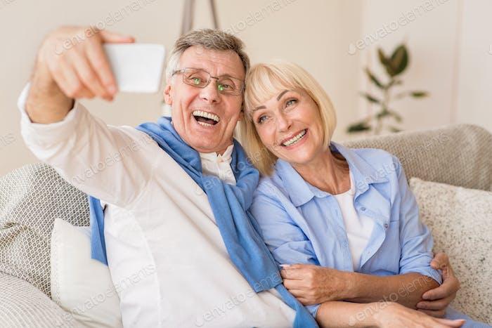 Modern grandparents taking selfie on cellphone, resting on sofa