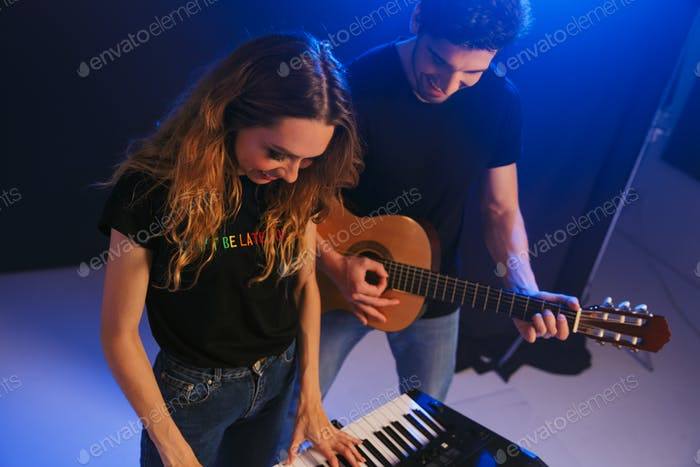 Couple musicians group duet on scene in night club over dark background with flash lights.