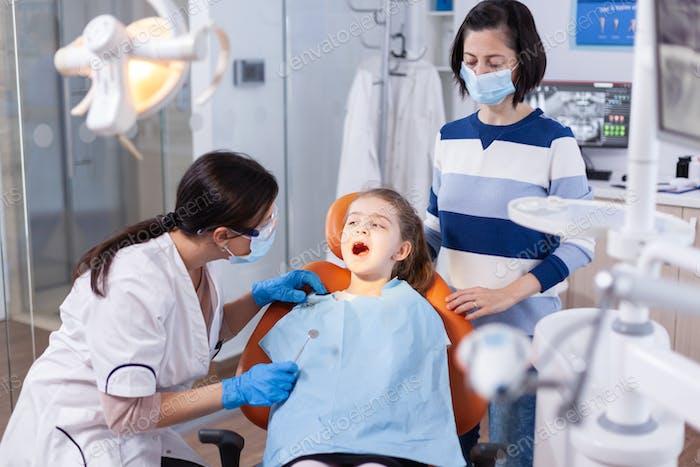 Dentist doing teeth check up of little girl