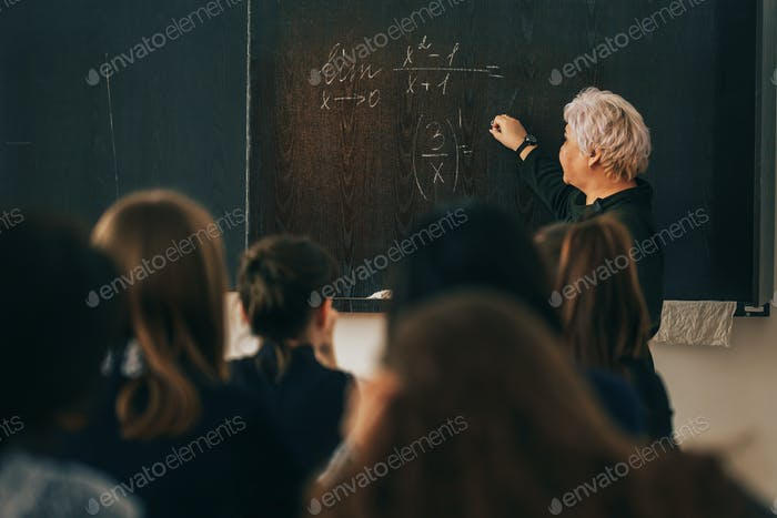 Woman teacher writes formula