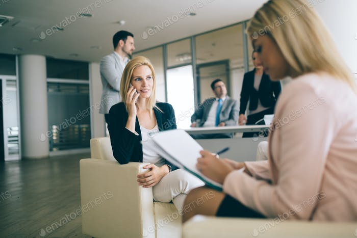 Happy young businesswomen doing paperwork in office