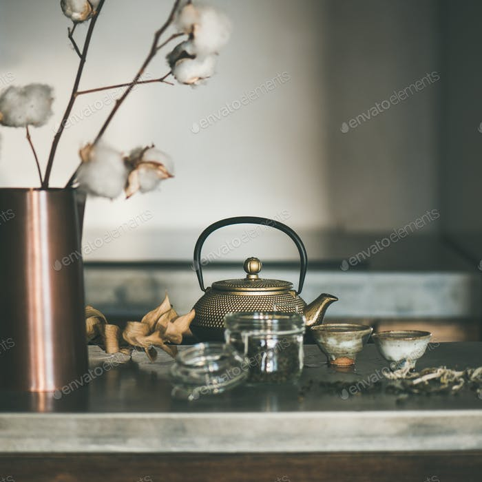 Golden teapot and cups on concrete counter, square crop