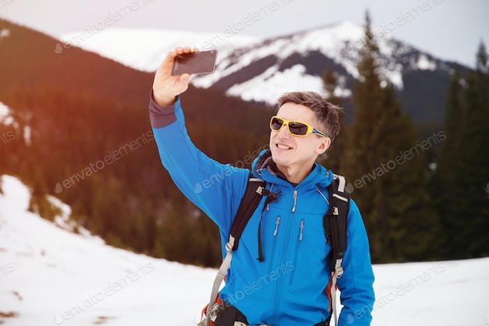 Hiker in winter mountains making selfie on smartphone