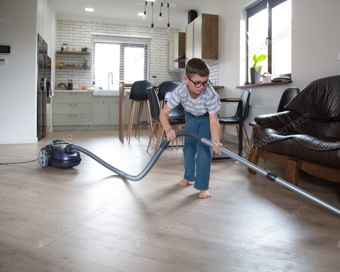 A little boy vacuums the room under the couch.