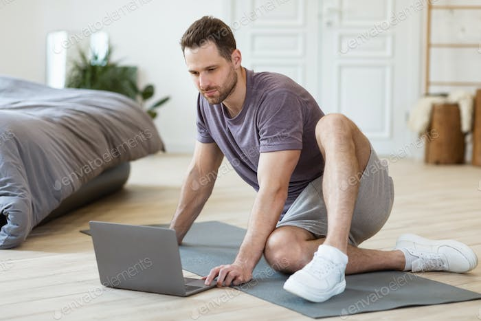 Man With Laptop Sitting On Mat Ready For Training Indoors