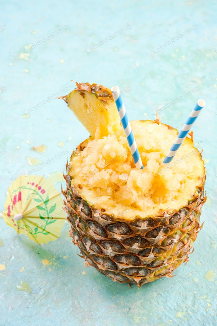 Serving tropical ice granita in pineapple