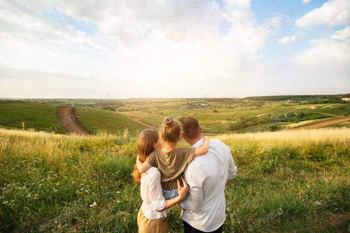 Happy family enjoying landscape outdoors in the field