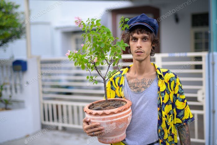 Portrait of young rebellious man holding pot of flowers outdoors