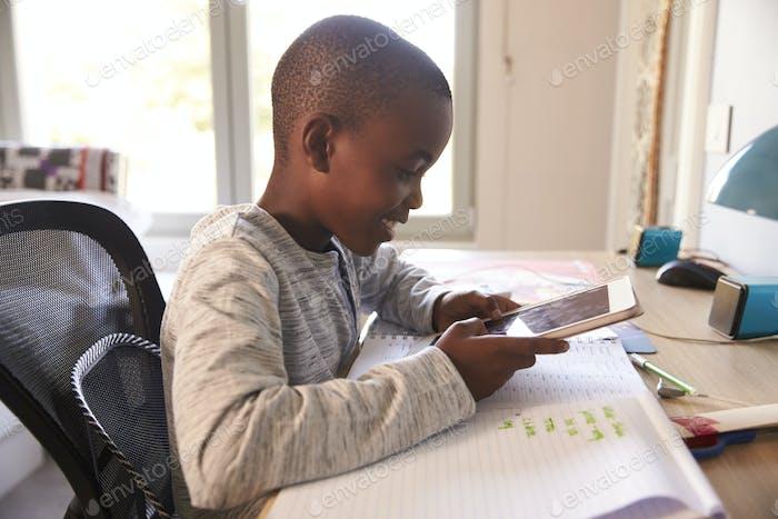 Junge im Schlafzimmer mit digitalem Tablet zu tun Hausaufgaben