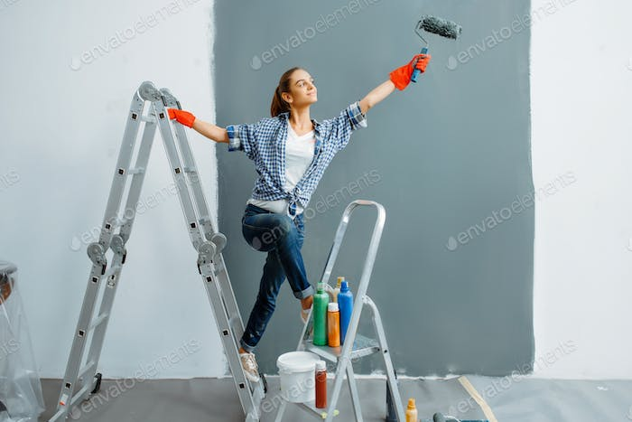 Cheerful female house painter paints walls indoor