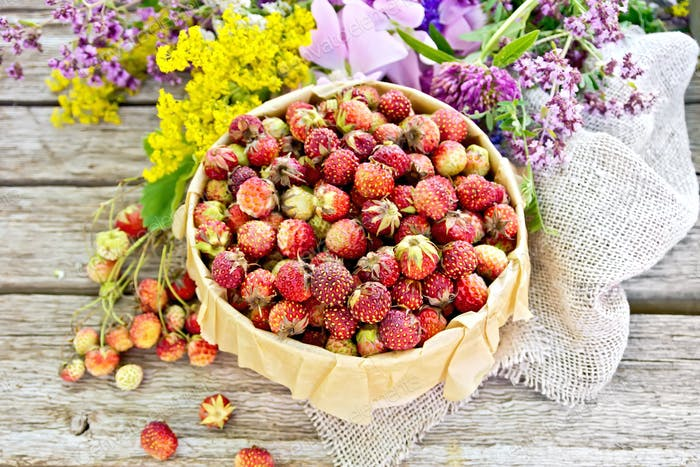 Strawberries in box with flowers on old board