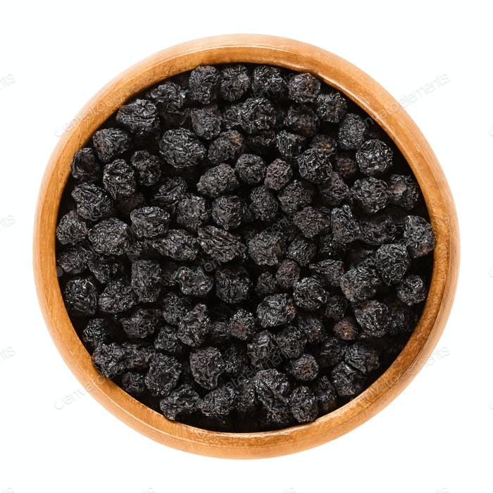 Aronia berries, black dried fruits in wooden bowl
