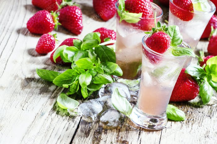 Pink cocktail with strawberry, basil, gin and ice