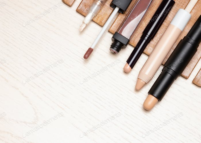 Different types of make-up concealers on white wooden table
