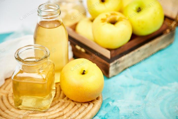 Glass Bottle of apple organic vinegar on blue background