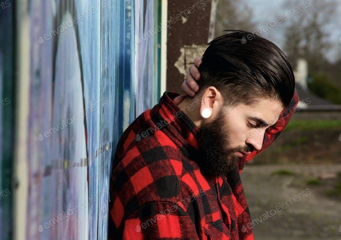 Hombre joven con barba y piercings al aire libre