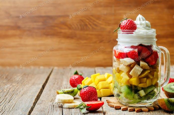 Kiwi strawberry banana mango salad with whipped cream.