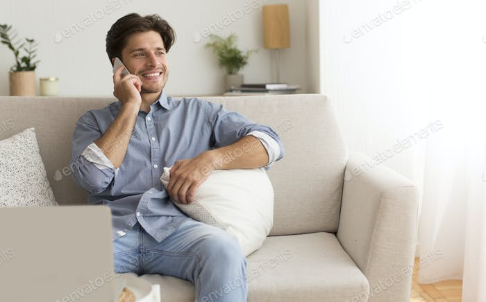 Positive Man Talking By Cellphone Sitting On Couch At Home