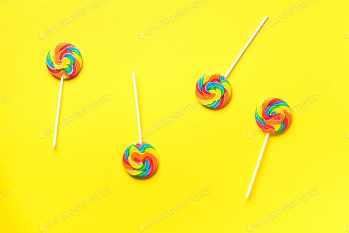 Round colorful lollipops on yellow background. Top view. Confetti for holidays, birthday party