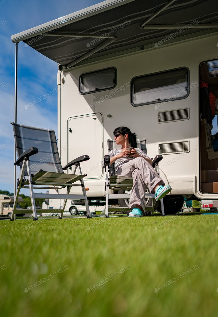 Thumbnail for Woman is standing with a mug of coffee near the camper RV.