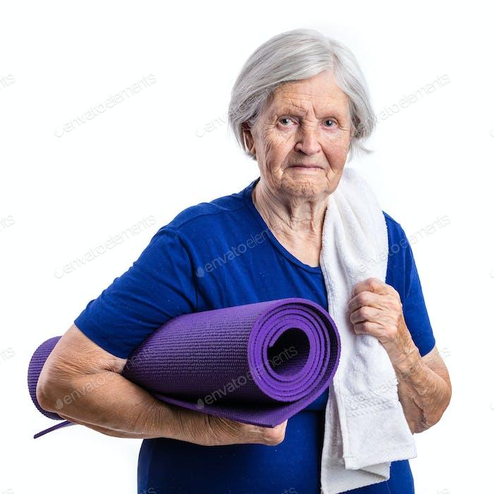 Senior woman holding yoga mat over white