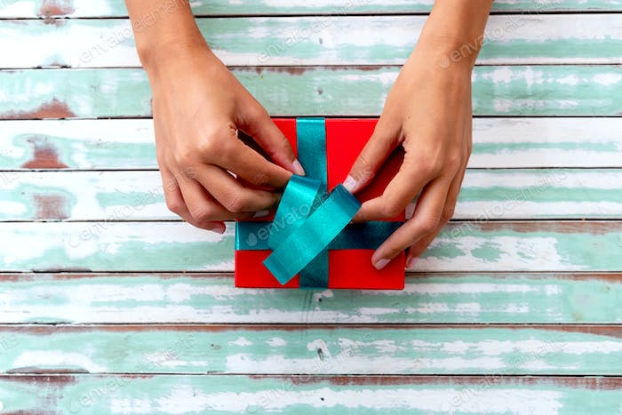 Detail of female hands wrapping gifts
