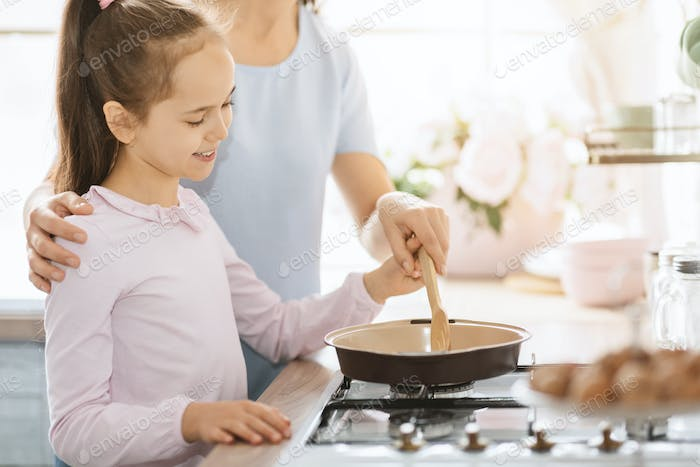 Cute little girl cooking together with mom